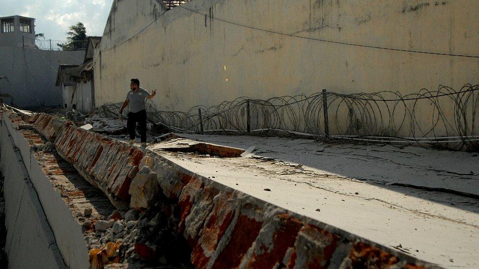 Policajac kod srušenog zida zatvora