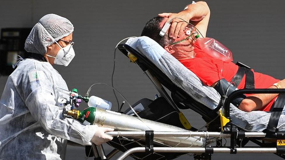 Profissional da saúde empurra paciente em maca