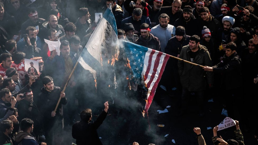 Manifestantes quemando banderas