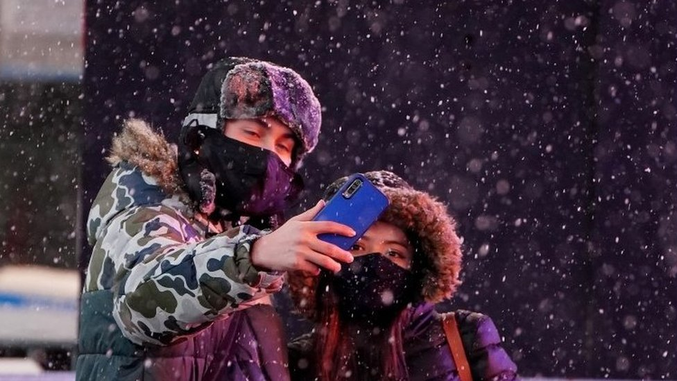 People take a selfie in Times Square in the snow