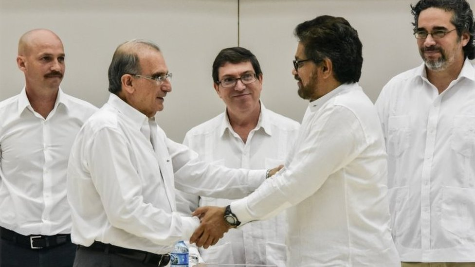 The head of the Colombian government delegation to the peace talks, Humberto de la Calle (L) and the head of the FARC-EP delegation Ivan Marquez (R) shake hands after the signing of the agreement on victims of the conflict at Convention Palace in Havana, on 15 December 2015