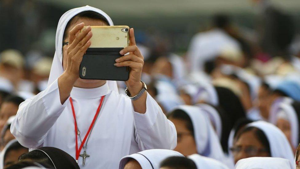Una monja tomando una foto con un iPhone