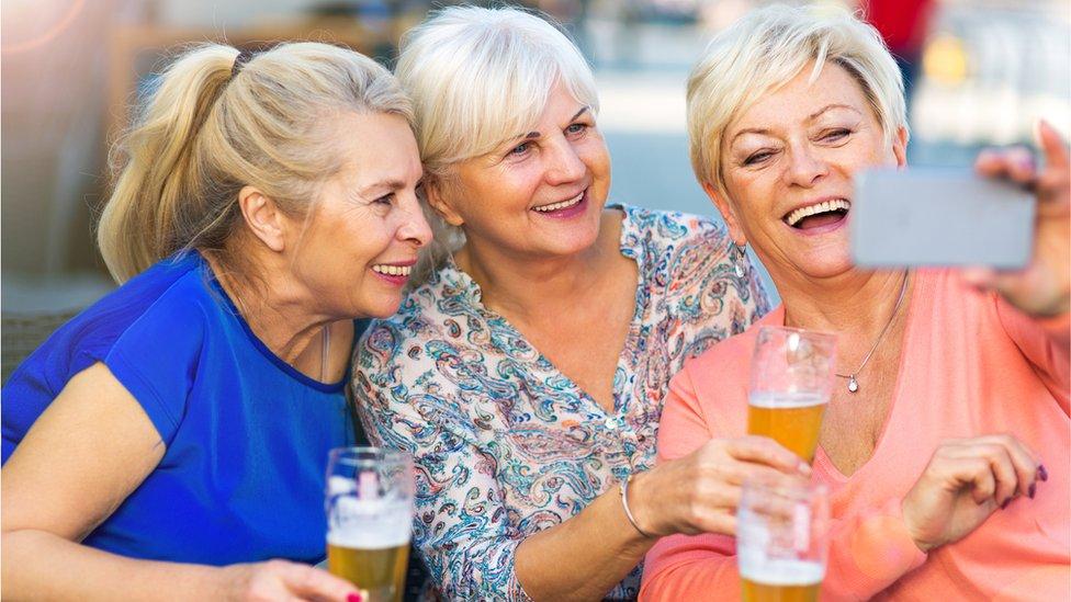 Mujeres riéndose tomándose un selfie.