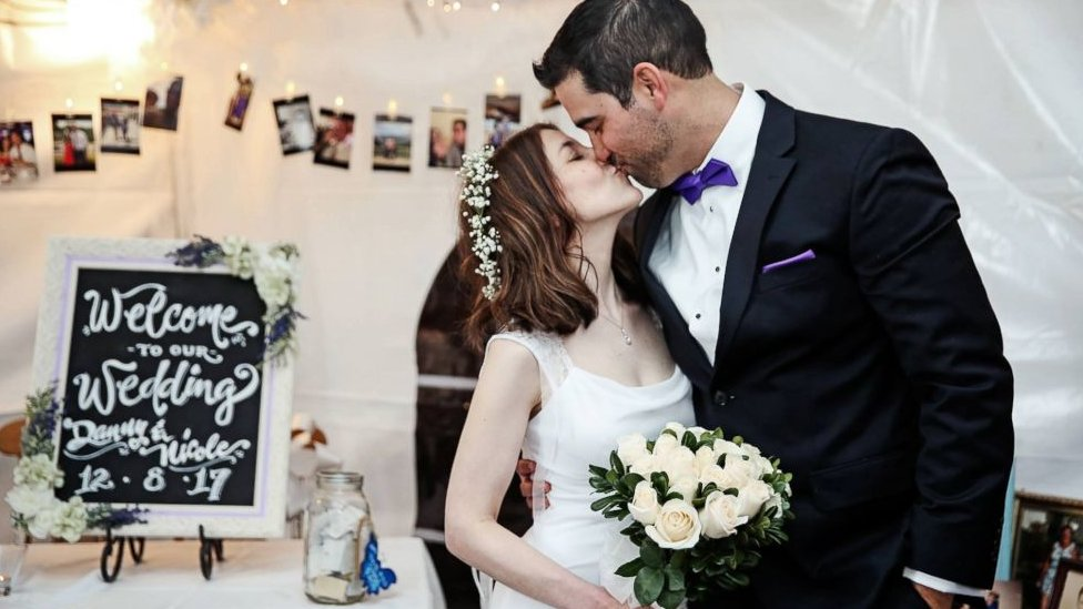 Nicole and Danny, in dress and tuxedo, kiss at their wedding