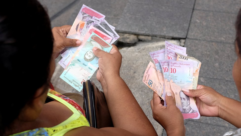 Venezuelan women hold the new currency, the sovereign bolivar, after its launch