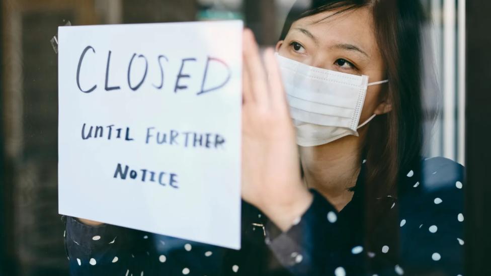 """Una mujer pega en una puerta un cartel de """"cerrado hasta próximo aviso""""."""