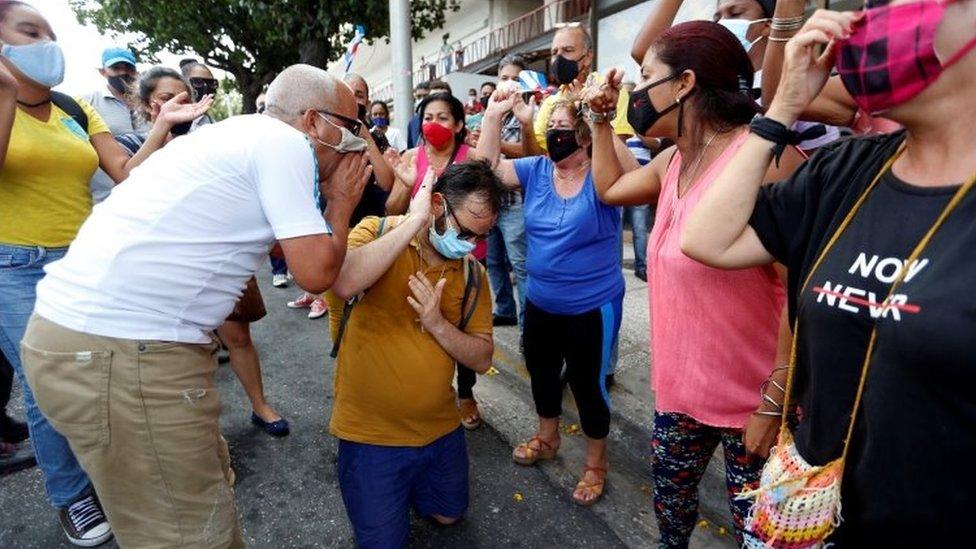 Manifestantes a favor del gobierno gritándole a un opositor