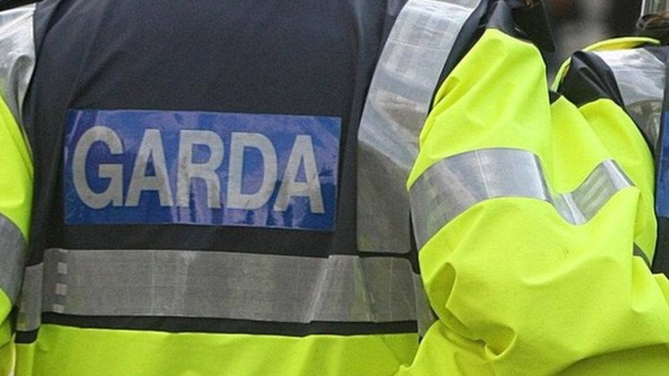 An officer wearing a coat marked: Garda