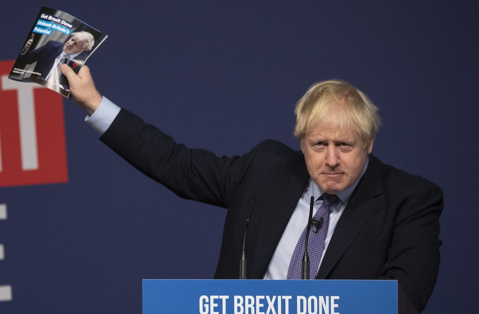 Boris Johnson waving the Conservative manifesto