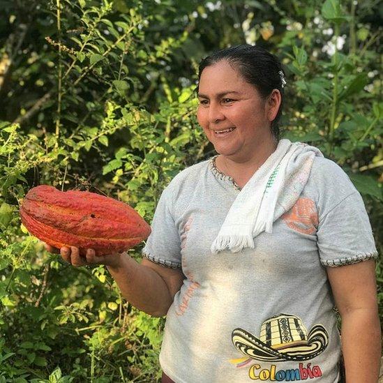 Ana Yudith, habitante de una de las comunidades alcanzadas por el proyecto, sosteniendo en su mano un fruto de cacao