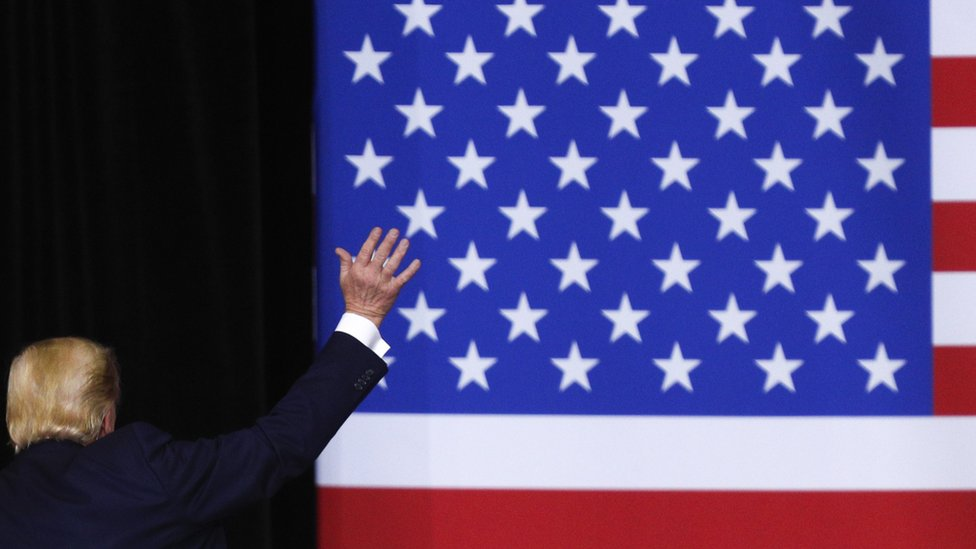 Donald Trump frente a una bandera de EE.UU.