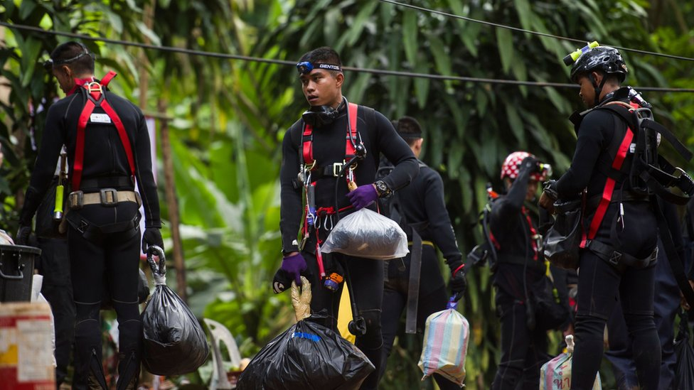 Thai divers carry supplies as rescue operations continue for 12 boys and their coach trapped at Tham Luang cave at Khun Nam Nang Non Forest Park in the Mae Sai district of Chiang Rai province on July 5, 2018.
