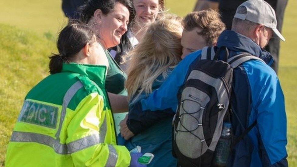Paramedics and first aiders attending to spectator