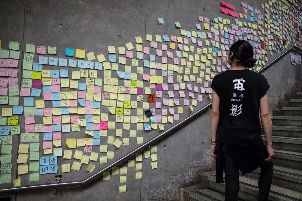 žena prolazi pored zida na kome su zalepljene poruke