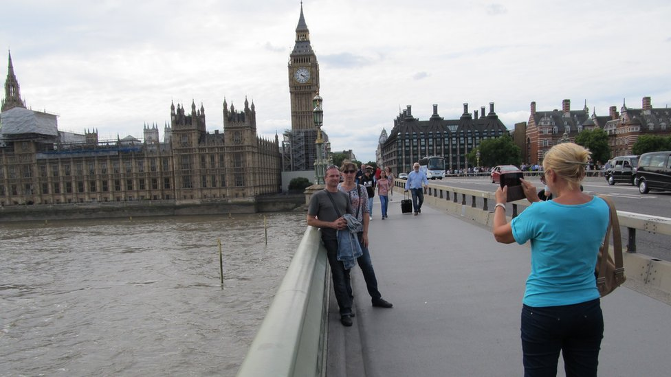 A woman taking a couple's photograph on Westminster Bridge
