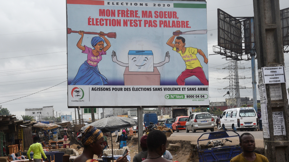 People walk past a billboard in Yopougon, a popular district of Abidjan, which promotes peaceful elections in Ivory Coast