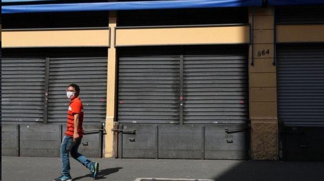 Homem caminha de máscara diante de lojas fechadas