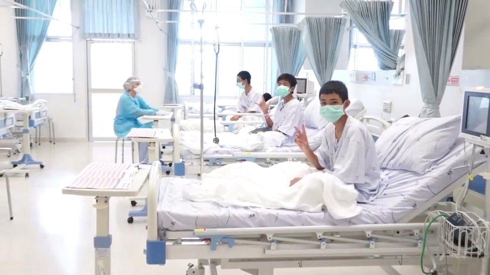 Boys rescued from the cave in Thailand sit up in their hospital beds and give victory signs