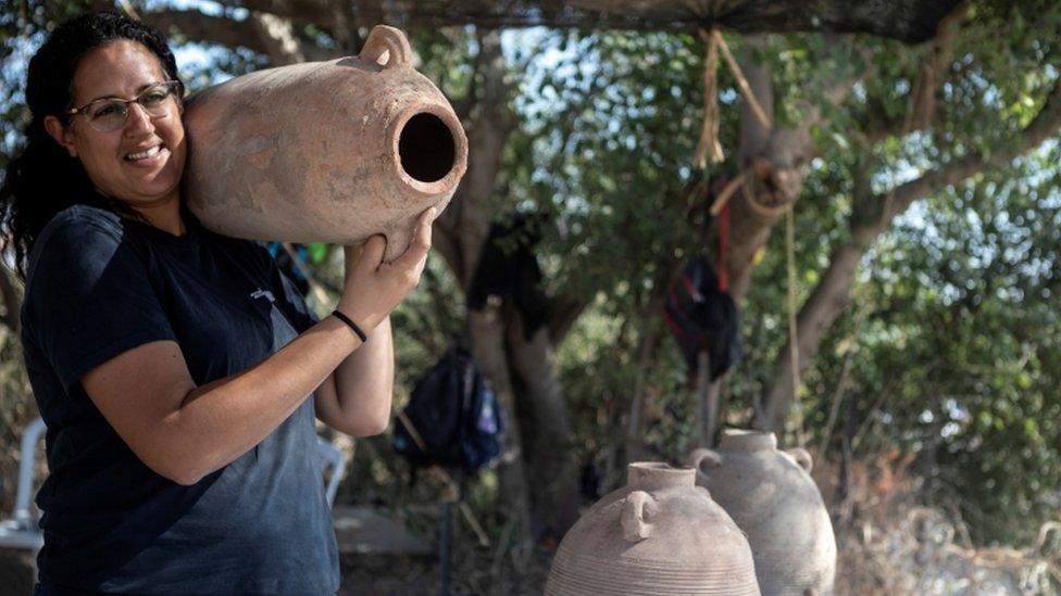 عالمة آثار تحمل جرة كانت تستخدم لتخزين النبيذ