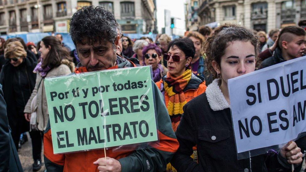 hombre sostiene pancarta en marcha feminista