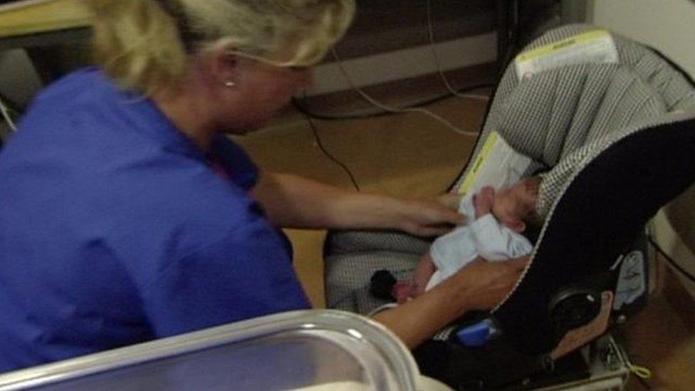 Nurse placing baby in car seat