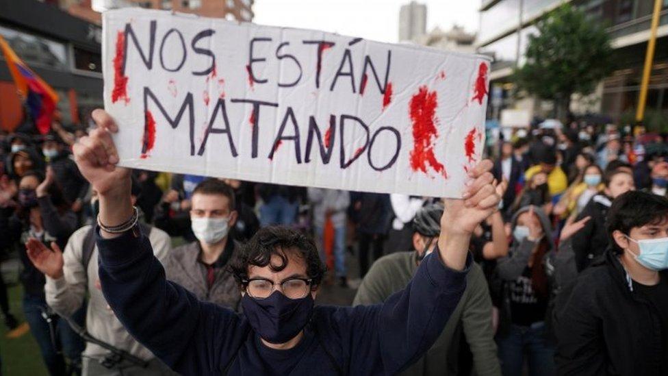 """Manifestante en Bogotá con un letrero que dice """"Nos están matando""""."""