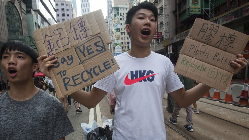 A protester encourages plastics recycling during the annual pro-democracy march, Wan Chai, Hong Kong, China, 01 July 2018.