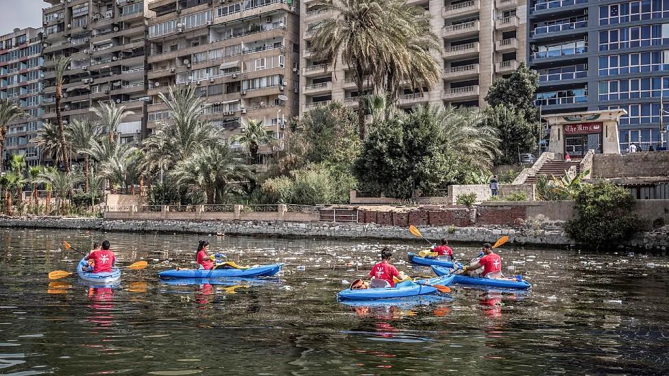 Voluntarios en kayaks recogiendo botellas de plástico en un río