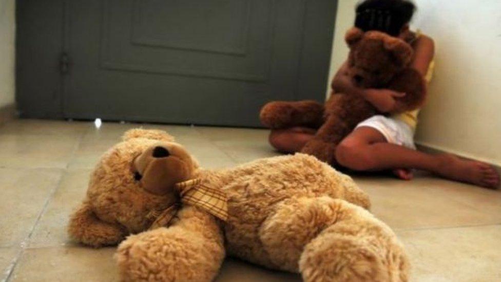 Niña sentada en una esquina de la sala con un oso en los brazos.
