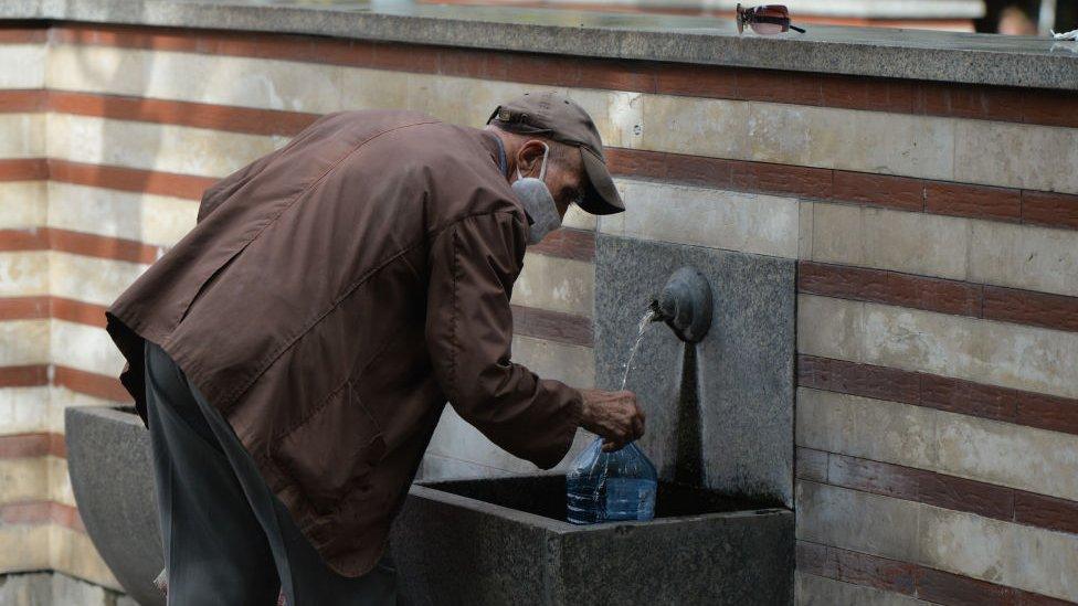 Hombre bebiendo agua de una fuente en Sofía, Bulgaria.