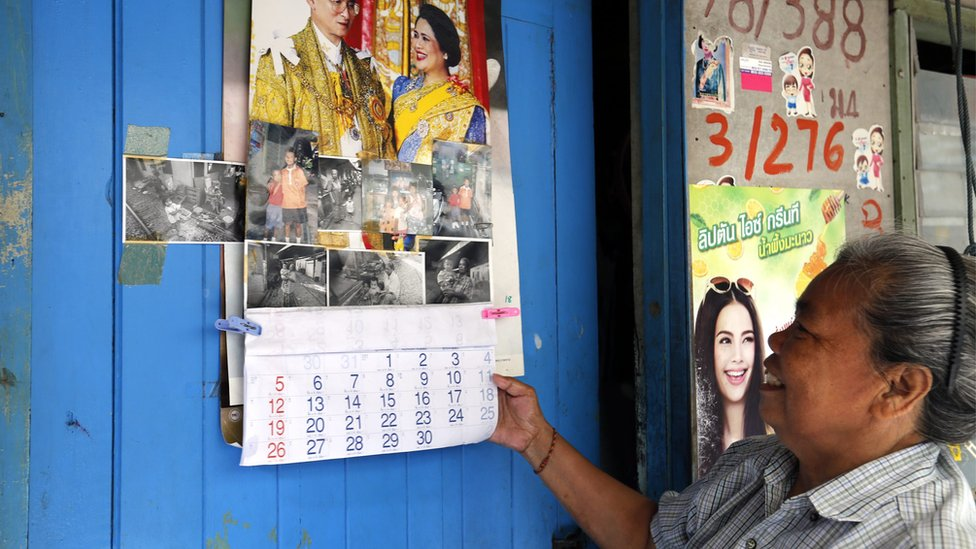Thai woman Ling Poomuang, 61, with a calendar showing Thai King Bhumibol Adulyadej, the world's longest-reigning monarch, and his wife Thai Queen Sirikit