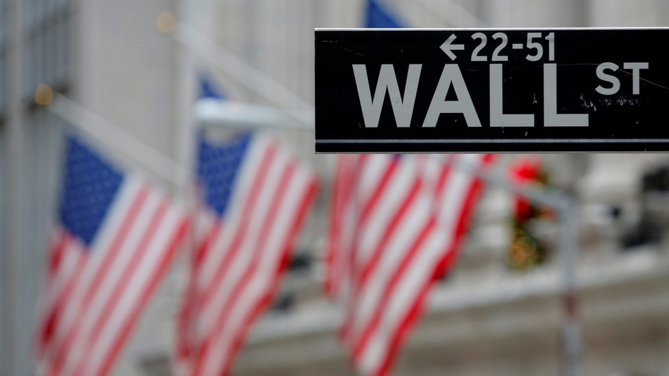 A street sign for Wall Street is seen outside the New York Stock Exchange (NYSE) in Manhattan, New York City, U.S. December 28, 2016