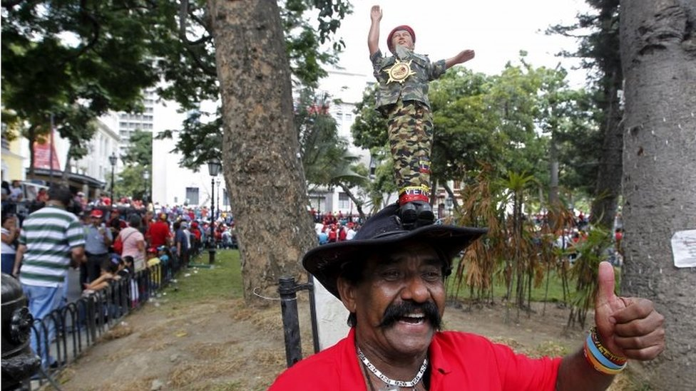 A supporter of Venezuela's President Nicolas Maduro, with a doll depicting late Venezuela's late president Hugo Chavez on his hat, reacts as he stands at the Plaza Bolivar near the building housing the National Assembly in Caracas on 5 January, 2016