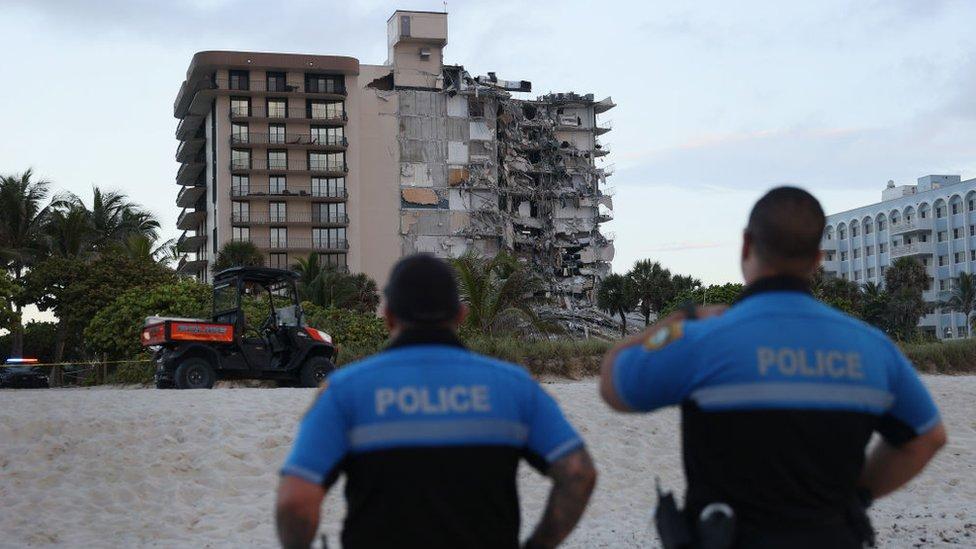 Policías miran el edificio derrumbado.