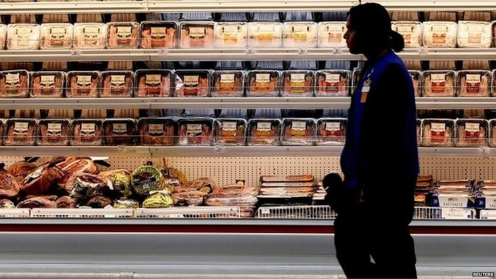 A employee walks by a meat cooler in the grocery section of a Sam's Club during a media tour in Bentonville, Arkansas, U.S. on June 5, 2014