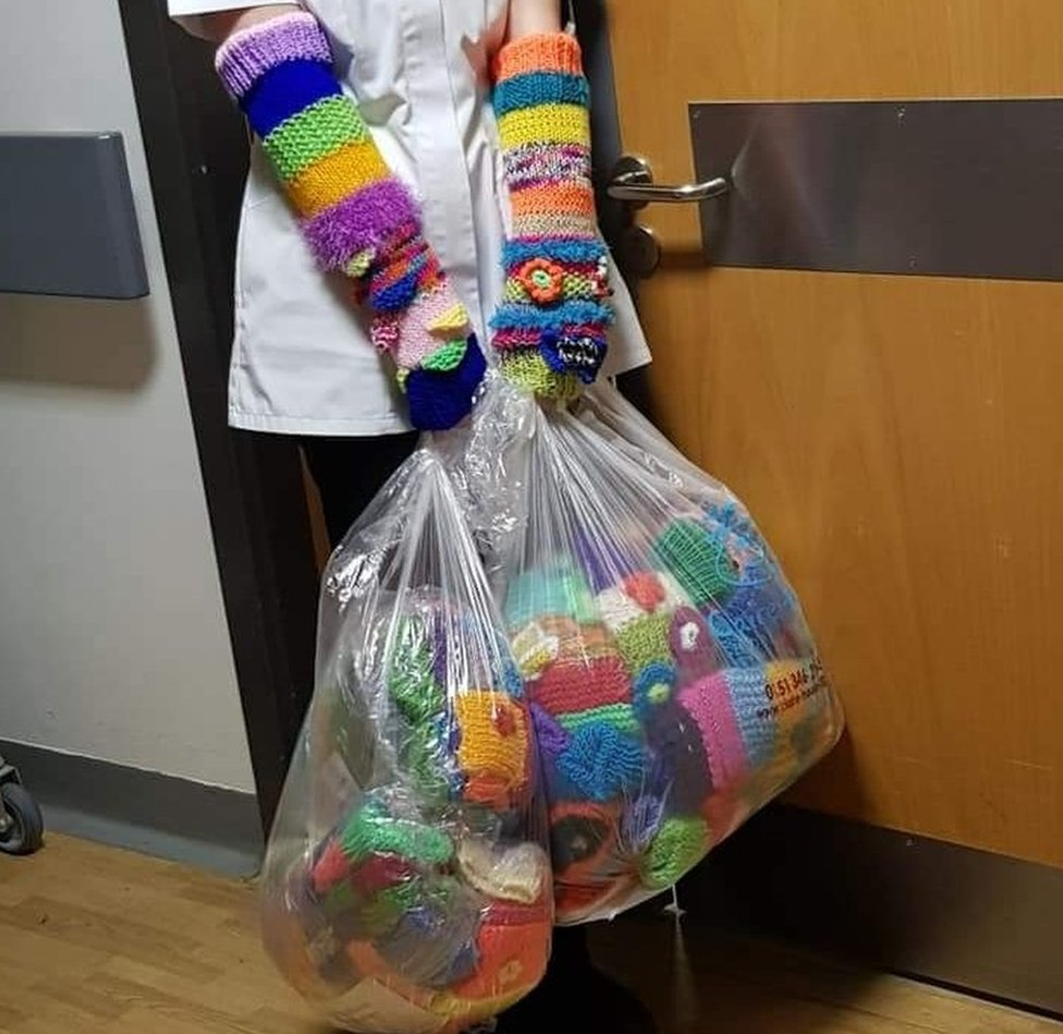 A nurse wears two sleeves, holding a bagful of sleeves as well