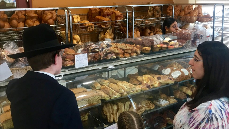 Two customers inside a bakery that has various breads and sweet pastries on display