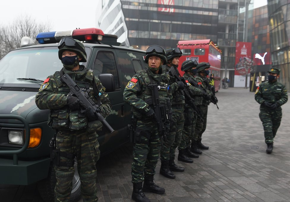 Armed police stand guard in the popular shopping and nightlife area of Sanlitun in Beijing on 26 December 2015.