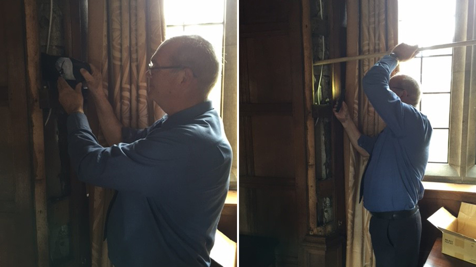Steve Beeby placing shoe behind panelling at St John's College