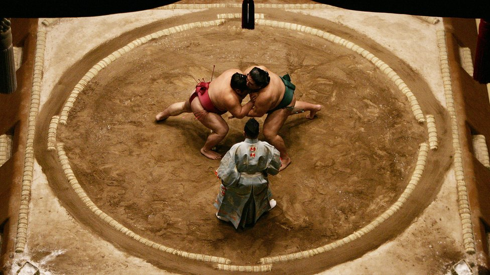 Sumo wrestlers Miyabiyama and Takekaze of Japan grapple each other in the middle of the ring during the Grand Sumo Championship