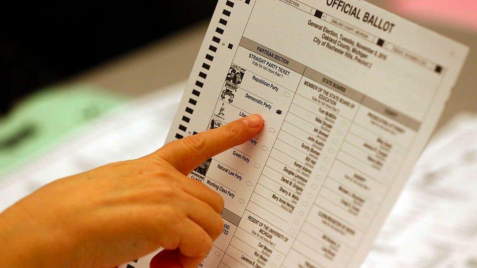Сотрудник избирательного отдела указывает на бюллетень на президентских выборах в США в 2016 году