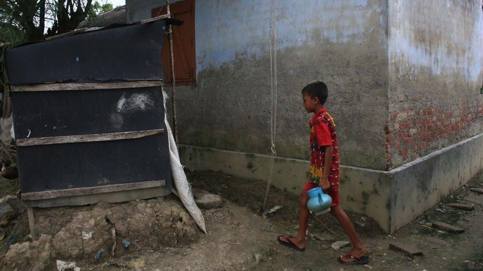 Boy preparing to use a makeshift bathroom in Bangladesh