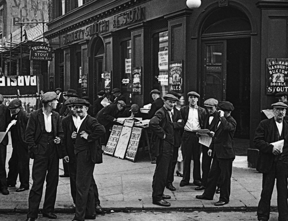 Working men gather outside a public house in Canning Town, London, 1935