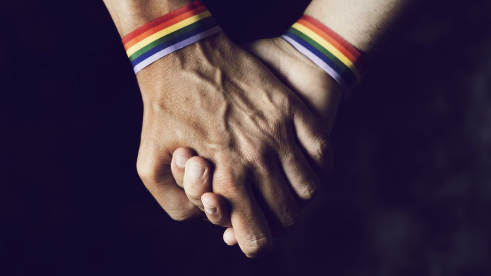 Men holding hands with rainbow-patterned wristband (file photo)