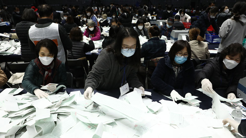 Officials from the South Korean Central Election Management Committee and election observers count votes