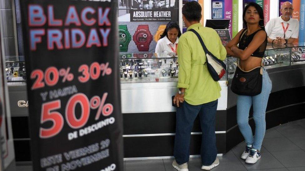 Un hombre y una mujer en una tienda de relojes con ofertas por el Black Friday