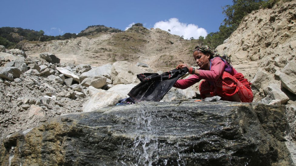 Woman washing clothes by the mountains water in town of Uttarkashi Uttarakhand, India, on 13 October 2018.