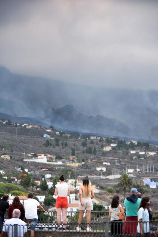 Personas observan la columna de humo del volcán La Palma, Canarias.