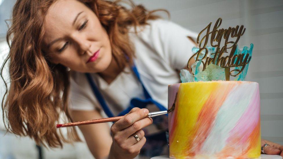 Mulher decorando bolo