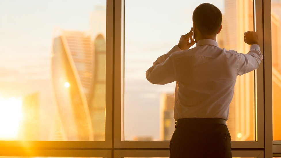 man at office window on mobile phone